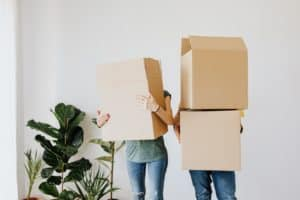 Woman and man holding boxes for moving preparations
